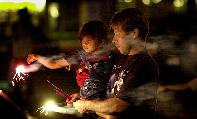 A man lights sparklers for a young girl